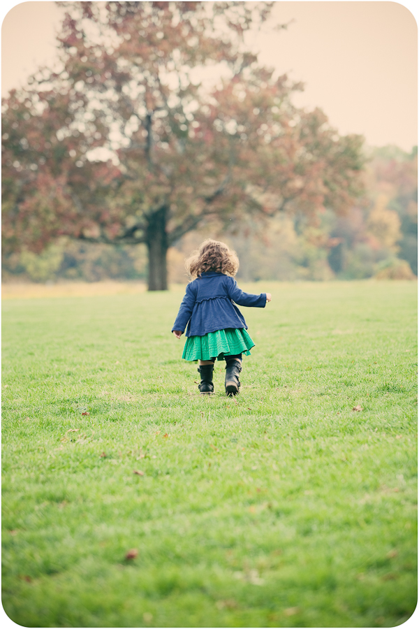 Photographer takes a portrait of little girl running on the lawns at Waveny House in New Canaan, CT
