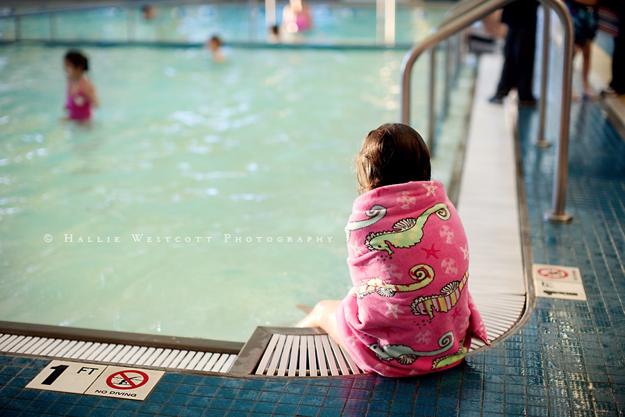 Little girl sits on the edge of a pool deep in thought as CT family photographer snaps her picture