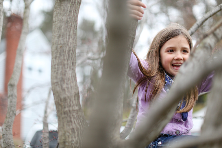 little girl in a tree during lifestyle family session in CT